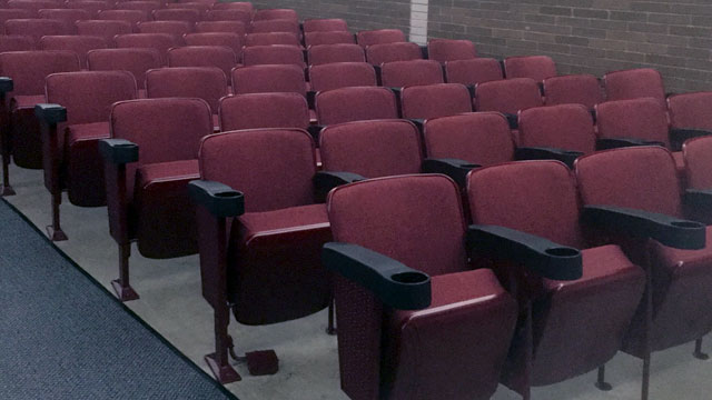 Reupholstering and restoration of (574) auditorium seats and installation of new Caddy armrests