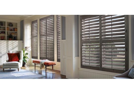 Teak solid wood shutters with grey stain add the finishing touch to this stunning room.  We can help you choose the perfect color.