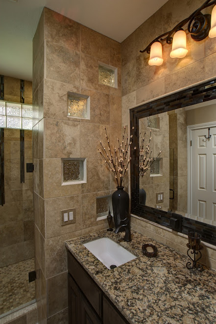 A custom walk in shower design accented with glass blocks, glass tile designs with travertine, frameless shower door, custom knotty alder vanity, and a framed beveled mirror.