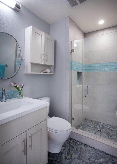 Part of a full house remodel with an addition, this guest bathroom was remodeled with a beach theme complete with glossy ripple glass tile and pebble flooring.