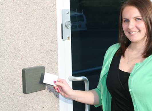 Employee of Atronic Alarms uses her card to access the reader to open the door to the building.