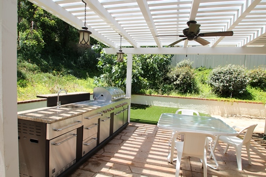 Part of a Whole house remodel and room addition for a multi-generational household the backyard was transformed into an outdoor kitchen complete with running water for a sink, refrigerator, gas cooktop, and a gas grill.