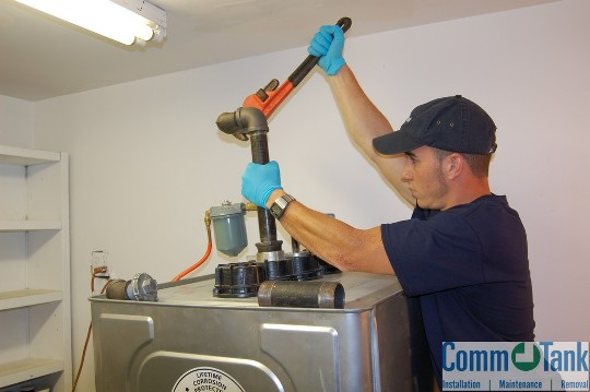 A CommTank employee is installing the vent line for a Roth oil tank.