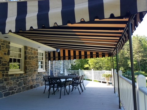 A beautiful black and tan stripe Sunbrella fabric canopy installed over a deck.