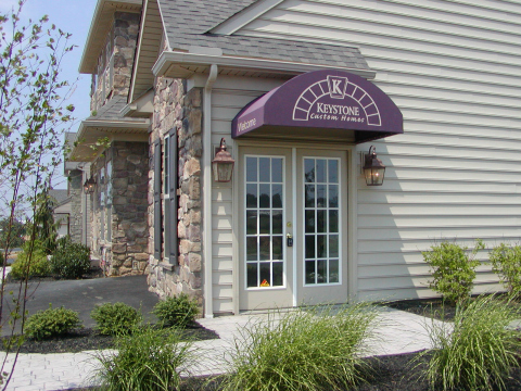 Doorhood awning installed over a model home show room - Keystone Custom Homes Sunbrella fabric cover