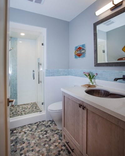 Part of a full house remodel with an addition, this guest bathroom was remodeled with a beach theme complete with a copper shell sink and pebble flooring.
