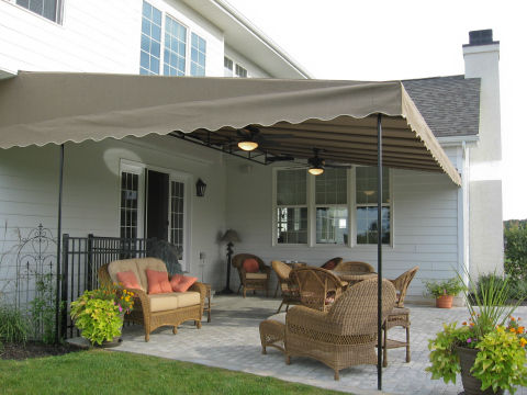 Sunbrella fabric canopy installed over a patio area featuring a powder coated frames and ceiling fans