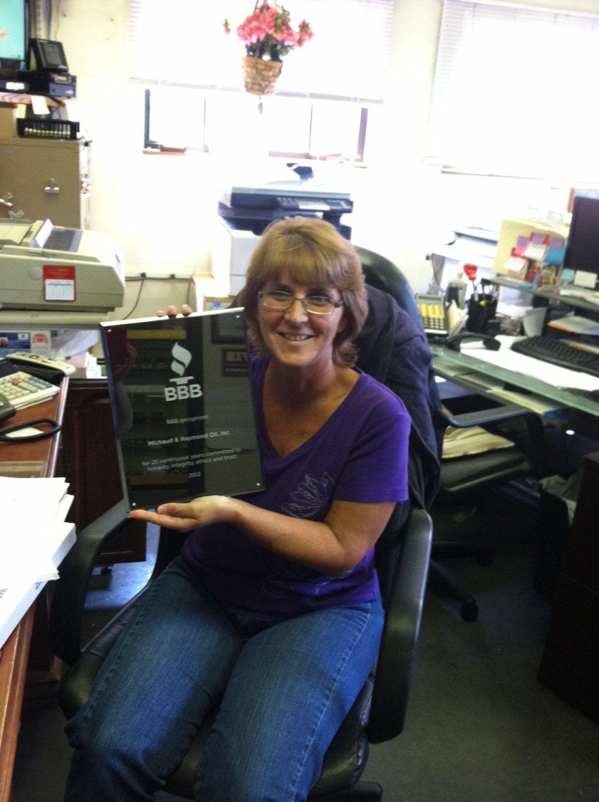 Office Manager Linda R., proudly diplaying a placque celebrating 25 years as an Accredited Business