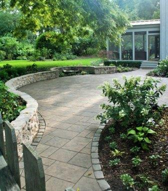 Large semi-permeable patio with seatwall and water feature