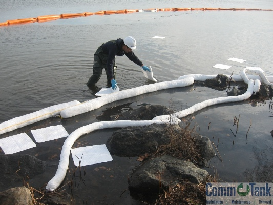 CommTank employee is spreading oil booms at a spill on Lake Quannapowitt.