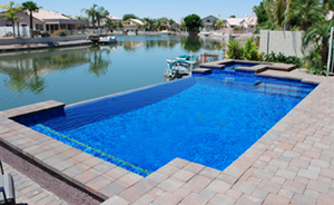 Remodel After - We created a negative edge, added a spa, refinished the pool with tile and installed a paver deck.